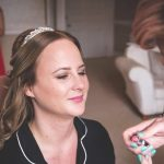 photo of bride on wedding day having make up applied